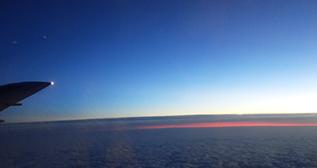 帰路の機窓から見た雲間の夕焼け